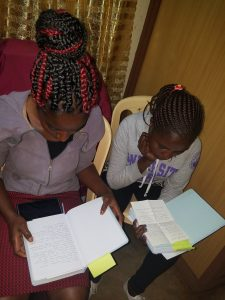 Mercy Merinyo and Loice Mucheni read their journals. They are part of the mentoring program.